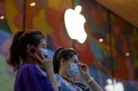 Women wearing masks to curb the spread of the coronavirus stand near new Apple store prepared for its opening in Beijing, China on July 14, 2020. (AP Photo/Ng Han Guan)