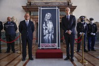 Franch Ambassador to Italy, Christian Masset, right, and Italian prosecutor Michele Renzo pose next to a recovered stolen artwork by British artist Banksy, depicting a young female figure with a mournful expression, that was painted as a tribute to the victims of the 2015 terror attacks at the Bataclan music hall in Paris, at the French Embassy in Rome, on July 14, 2020. (AP Photo/Domenico Stinellis)