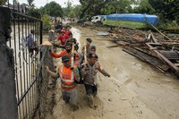 Rescuers wade through mud as they carry the body of a victim at an area affected by flash flood in Baebunta, South Sulawesi province, Indonesia, on July 14, 2020. (AP Photo)