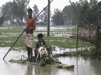 In this video grab taken from the Associated Press Television footage, Bangladeshi men with a goat row a banana raft through flood waters in Lalmonirhat, Bangladesh, on July 13, 2020. (AP Photo/Bayezid Ahmed)