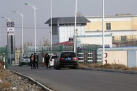 In this Dec. 3, 2018 file photo, people walk by a police station near the front gate of the Artux City Vocational Skills Education Training Service Center in Artux in western China's Xinjiang region. (AP Photo/Ng Han Guan)