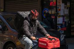 海外でもマスクを着けて注文料理を配達(Bloomberg)