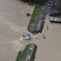 堤防が決壊し、浸水地域から(右)から球磨川に流れ込む水=熊本県人吉市中神町で2020年7月4日、本社ヘリから田鍋公也撮影