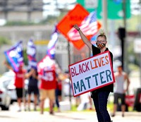 A Black Lives Matter protester salutes passing traffic while supporters of President Donald Trump rally in the background at the intersection of U.S. 17-92 and S.R. 436 in Casselberry, Fla., on July 14, 2020. (Joe Burbank/Orlando Sentinel via AP)