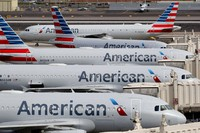 In this March 25, 2020, file photo, American Airlines jets sit idly at their gates as a jet arrives at Sky Harbor International Airport in Phoenix. American Airlines is telling 25,000 workers that they could lose their jobs in October because of the sharp drop in air travel during the virus pandemic. (AP Photo/Matt York)