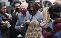Actor Johnny Depp, center, is surrounded by fans as he arrives at the High Court in London, on July 16, 2020. (AP Photo/Alastair Grant)