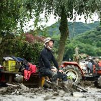 土砂をかき出す作業の手を休め、腰をおろす尾方広海さん=熊本県人吉市で2020年7月15日午後4時49分、徳野仁子撮影