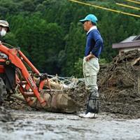 自宅の敷地にたまった土砂の処理について話し合う尾方和敏さん(右)と息子の広海さん=熊本県人吉市で2020年7月15日午後4時39分、徳野仁子撮影