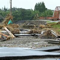 球磨川に架かる天狗橋に続く道はアスファルトがはがれ、橋の一部は崩落した=熊本県人吉市で2020年7月16日午前10時52分、徳野仁子撮影