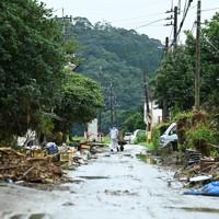 道路が泥で覆われ、電信柱などに流木がたまった大柿地区=熊本県人吉市で2020年7月16日午前9時56分、徳野仁子撮影
