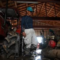 ふくらはぎまで泥に覆われた農機具小屋にたたずむ尾方和敏さん。自宅は2階の屋根近くまで浸水し、農機具小屋は完全に水没。「もうここに住むことは考えられん」とつぶやいた=熊本県人吉市で2020年7月14日、徳野仁子撮影