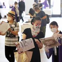 フェースシールド、マスク、手袋を着用して観客の案内をするスタッフ=東京・両国国技館で2020年7月19日午後1時21分、長谷川直亮撮影