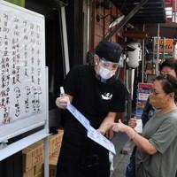 フェースシールドを装着して接客するウナギ専門店の従業員=大阪市生野区の「舟屋」で2020年7月21日午前9時28分、平川義之撮影