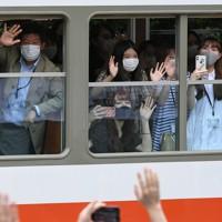 2019年の台風19号の被害で一部運休していた箱根登山鉄道が全線で運行を再開し、車内から手を振る乗客ら=神奈川県箱根町で2020年7月23日午前10時39分、北山夏帆撮影