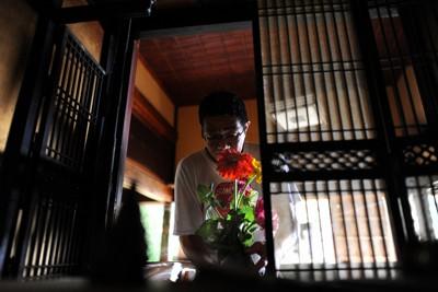 全壊した自宅内で届けられた切花を、津波で流され枠だけが残る仏壇に飾る男性=岩手県大船渡市で2011年8月2日、宮間俊樹撮影