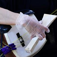 感染症対策として、ビニールの手袋をつけて三味線のバチを持つ=大阪市天王寺区で、木葉健二撮影