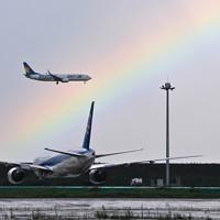 強い雨の後、羽田空港で見られた虹の中を着陸する旅客機=東京都大田区で2020年7月26日午後4時10分、手塚耕一郎撮影