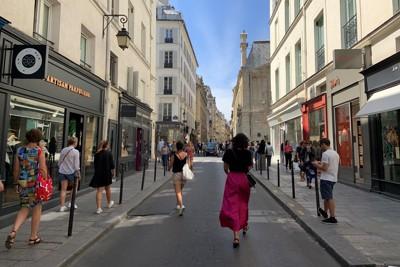 ブティックが立ち並ぶマレ地区の通り。入店の際にはマスクの着用が求められるので、手にブラブラ持って歩く人も=パリ市内で筆者撮影