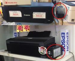 非純正インクタンク(〇印)を外付けした改造品(上)に対抗し、純正インクタンク(〇印)を外付けした製品を開発