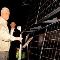 浮島太陽光発電所を訪れ、展示用の実物パネルの前で説明を受ける台湾の李登輝元総統(左から2人目)=川崎市川崎区浮島町で2014年9月22日、鈴木玲子撮影
