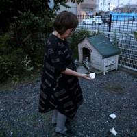 爆発事故が起きた店舗(奥)から近い自宅の庭で、飛んできた建物の破片を拾う女性。「ものすごい音で、店側の家の窓ガラスがほとんど割れましたよ」=福島県郡山市で2020年7月30日午後7時12分、和田大典撮影