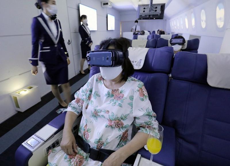 VRゴーグルを装着して海外旅行の気分を味わう利用者ら=東京都豊島区で2020年7月3日、宮武祐希撮影