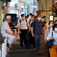 東京都内で新型コロナウイルスの新規感染者数が最多を更新する中、ガード下の居酒屋の前を通り、マスクを着けて足早に新橋駅方面に向かう人たち=東京都港区で2020年7月31日午後6時8分、手塚耕一郎撮影