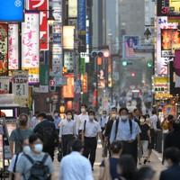 東京都内で新型コロナウイルスの新規感染者数が最多を更新する中、繁華街を抜けて新橋駅へと向かう通勤者ら=東京都港区で2020年7月31日午後6時16分、手塚耕一郎撮影