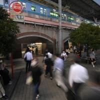 東京都内で新型コロナウイルスの感染者数が最多を更新する中、足早に新橋駅に向かう人たち=東京都港区で2020年7月31日午後7時2分、手塚耕一郎撮影