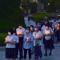 ろうそくを手に平和記念公園内を行進する参加者たち=広島市中区で2020年7月31日午後7時25分、藤井達也撮影
