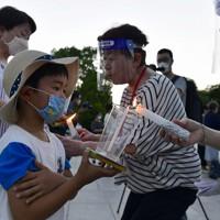 「平和の灯」を受け取る参加者=広島市中区で2020年7月31日午後7時13分、藤井達也撮影