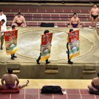 幕内前半の取り組み終了後に掲げられた新型コロナウイルス感染への警戒を呼びかける垂れ幕=東京・両国国技館で2020年7月31日、滝川大貴撮影