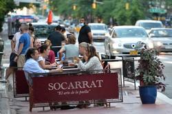 屋外飲食ができるようになり、レストラン前に設けられたテーブルで談笑する市民=米ニューヨークで2020年6月22日、隅俊之撮影