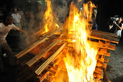 精霊の「迎え火」として燃え上がる震災遺族らのメッセージが書かれたまき=岩手県陸前高田市で2011年8月8日午後7時10分、大西岳彦撮影