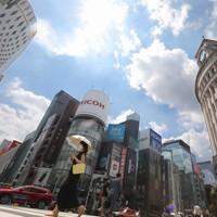 強い日差しが照りつける中、日傘をさして歩く人たち。気象庁は関東甲信と東海で梅雨明けしたとみられると発表した=東京都中央区で2020年8月1日午後1時8分、喜屋武真之介撮影
