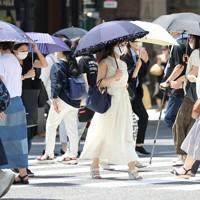 強い日差しが照りつける中、日傘をさして歩く人たち=東京都中央区で2020年8月1日午後0時55分、喜屋武真之介撮影