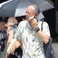 強い日差しが照りつける中、信号待ちの間に汗を拭う通行人=東京都中央区で2020年8月1日午後0時52分、喜屋武真之介撮影