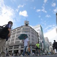 強い日差しが照りつける中、日傘をさして歩く人たち=東京都中央区で2020年8月1日午後2時37分、喜屋武真之介撮影