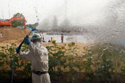 防護服を着て小学校の窓を高圧洗浄機で洗い流し、除染する作業員=福島県南相馬市の鹿島小学校で2011年8月12日、竹内幹撮影