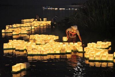 夕闇の中、名取川に流されるたくさんの灯籠=宮城県名取市で2011年8月13日午後7時23分、手塚耕一郎撮影