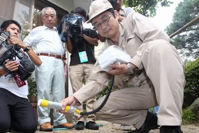 福島第1原発事故による空間線量調査のため、住宅の庭で放射線量を調査する県職員=福島市渡利で2011年8月18日午前9時半、武市公孝撮影