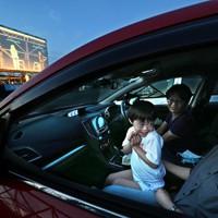 駐車中の車内でドライブインシアターを楽しむ家族=大阪府吹田市で2020年8月1日午後7時13分、山崎一輝撮影