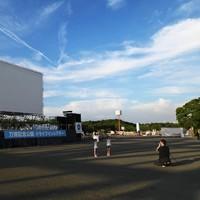 万博記念公園のドライブインシアターの開幕を前に、太陽の塔のまねをして記念撮影する子どもたち=大阪府吹田市で2020年8月1日午後6時5分、山崎一輝撮影