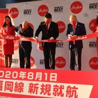 福岡便就航を祝いテープカットするエアアジア・ジャパンの会田純COO(中央)ら関係者=中部空港で