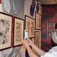 「進撃の巨人展FINAL」で展示中の原画を撮影するファン=神戸市中央区明石町で、中田敦子撮影