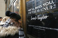 In this Jan. 2, 2019, file photo, women peer in the front door of Lord & Taylor's flagship Fifth Avenue store which closed for good in New York. (AP Photo/Kathy Willens)