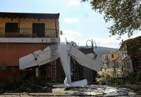 A small plane lays on a building after a crash in the village of Proti, near Serres town, northern Greece, on Aug. 3, 2020. (Ilias Kotsireas/InTime News via AP)