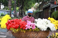 A flower vender wearing a face mask to protect against the coronavirus waits for customers in Hanoi, Vietnam, on Aug. 3, 2020. (AP Photo/Hau Dinh)