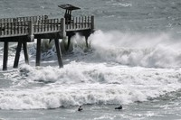 A pair of surfers paddle out as incoming waves break at the end of the Jacksonville Beach Fishing Pier on Aug. 3, 2020, in Jacksonville, Florida. (Bob Self/The Florida Times-Union via AP)