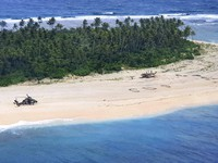 In this photo provided by the Australian Defence Force, an Australian Army helicopter lands on Pikelot Island in the Federated States of Micronesia, where three men were found, on Aug. 2, 2020, safe and healthy after missing for three days. (Australian Defence Force via AP)